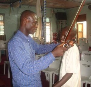 Titus helping a young violinist